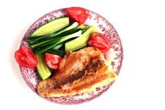 Filé av Fried fisken på en platta med gurkor, tomater, lökar och gaffeln Royaltyfri Bild