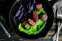 Filé av lammet Mosade ärtor bakad purpurfärgad potatis Royaltyfri Foto
