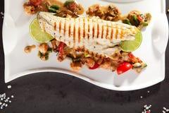 Filé av seabassen med grönsaker arkivfoto