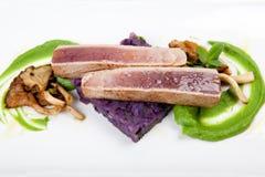 Filé av tonfisk med purpurfärgade potatisar, champinjoner och blödiga ärtor Arkivfoto