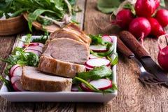 Filé för stekgriskött med med arugula- och rädisasallad royaltyfri foto