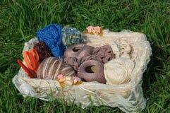 Fil à tricoter dans le panier sur l'herbe verte Photographie stock