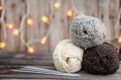 Fil à tricoter et aiguilles sur le fond en bois Photos stock