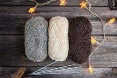 Fil à tricoter et aiguilles sur le fond en bois Photo stock