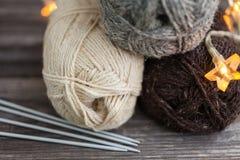 Fil à tricoter et aiguilles sur le fond en bois Photographie stock libre de droits