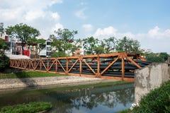 Fil électrique noir empilé sur la rivière de croisement de rail en métal dans la ville Photographie stock libre de droits