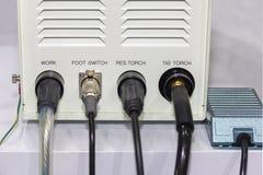 Fil électrique relié à la boîte de contrôle de la machine de soudure de chat et du commutateur de pied sur la table dans l'usine image stock
