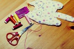 Fil, aiguilles, ciseaux et un jouet sur la table Photos libres de droits