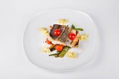 Filé av stekt torsk med grönsaker på den vita plattan Royaltyfri Fotografi