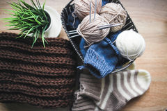 Fil beige, blanc et bleu, aiguilles de tricotage dans le panier et une écharpe brune Photographie stock