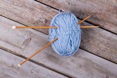 Fil bleu avec les aiguilles de tricotage en bois Photographie stock libre de droits