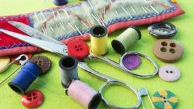 Fil, ciseaux, aiguilles et boutons sur la table verte Photo stock