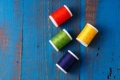 Fil coloré dans la bobine pour coudre, sur un backg en bois bleu Images libres de droits