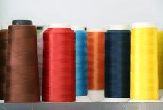 Fil coloré dans le petit pain de fil, couleur rouge, brun, bleu, bleu-foncé, orange, jaune et rose Image stock