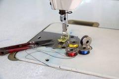 Fil coloré dans les bobines, la couleur bleue et blanche jaune rouge, avec des ciseaux Clippers mis sur la machine à coudre Photos stock