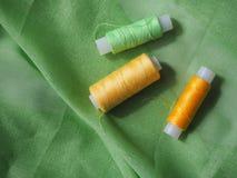 Fil coloré de bobine sur le tissu vert Photos stock