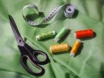 Fil coloré de bobine sur le tissu vert Images libres de droits