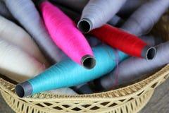 Fil coloré de bobines dans le panier en bois Images stock