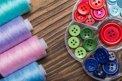 Fil coloré et boutons colorés sur un fond en bois Photo libre de droits