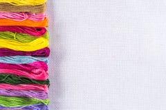 Fil coloré pour la broderie sur la toile blanche Copiez le spase Image stock