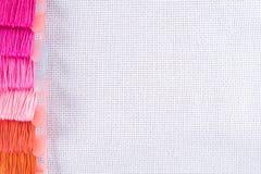 Fil coloré pour la broderie sur la toile blanche Copiez le spase Photo stock