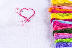 Fil coloré pour la broderie sur la toile blanche, une aiguille avec le fil rouge sous forme de coeur Le concept de l'amour pour u Images libres de droits