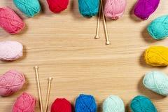 Fil coloré pour tricoter et aiguilles de tricotage sur le fond en bois Photos libres de droits