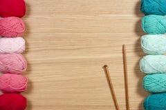 Fil coloré pour tricoter et aiguilles de tricotage sur le fond en bois Image stock