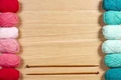 Fil coloré pour tricoter et aiguilles de tricotage sur le fond en bois Images stock
