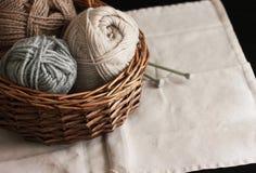 Fil d'Ecru, brun et gris de laine avec des aiguilles dans le panier en bois Image libre de droits