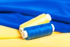 Fil de bleu et de jaune sur le tissu Photos stock