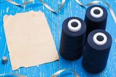 Fil de bobine et papier bleus de vintage sur la table Copiez l'espace Photographie stock libre de droits