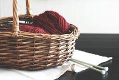 Fil de Bourgogne de laine avec des aiguilles dans le panier en bois Images libres de droits