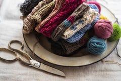 Fil de couleur pour tricoter, poignet tricot? dans le plat de cru d'?mail sur le tissu de toile avec des ciseaux de cru photographie stock libre de droits