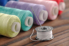 Fil de couture et bobine colorés sur un fond en bois Images libres de droits