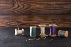 Fil de couture sur des bobines, tissu, aiguilles pour coudre sur le fond en bois Placez pour la mise sur pied des produits, le tr Photos stock