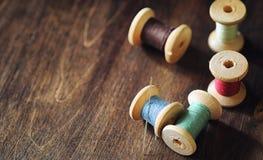 Fil de couture sur un fond en bois Ensemble de fils sur des bobines image libre de droits