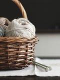 Fil de laine beige dans le panier en bois brun avec des aiguilles de tricotage Image libre de droits