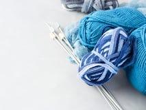 Fil de laine bleu avec des aiguilles de tricotage sur le fond gris Photographie stock libre de droits