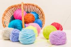 Fil de laine coloré emietté du panier en osier Image stock