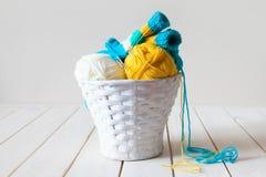 Fil de laine dans les bobines et embrouillements dans un panier blanc Une table faite Photo libre de droits