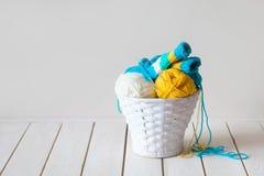 Fil de laine dans les bobines et embrouillements dans un panier blanc Une table faite Image libre de droits