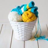Fil de laine dans les bobines et embrouillements dans un panier blanc Une table faite Images libres de droits