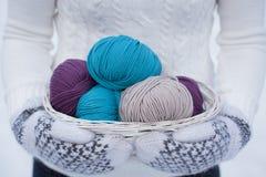 Fil de laine dans un panier blanc Blanc et mitaines de laine tricotées par brun Images libres de droits