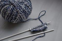 Fil de laine de mélange et modèle tricoté sur des aiguilles de tricotage Photo stock
