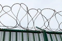 Fil de rasoir sur la barrière verte gardant le terminal du ferry français Image libre de droits