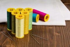 Fil et aiguille de couture multicolores de concept de DIY sur en bois blanc Photographie stock libre de droits