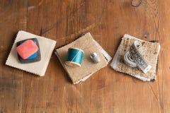 Fil et aiguille, ruban métrique et craie sur des échantillons de tissu Images libres de droits