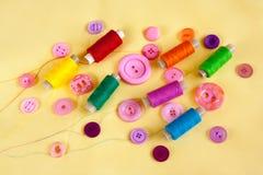 Fil et boutons de couture sur le tissu jaune Images stock