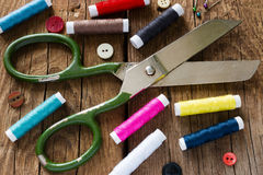 Fil et ciseaux colorés sur l'en bois un fond Image stock